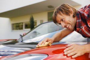 Man proudly polishing hi electric car --- Image by © Matelly/cultura/Corbis